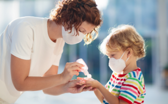 Mother and child wearing masks and using hand sanitizer