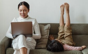 woman using laptop while sitting on couch next to child